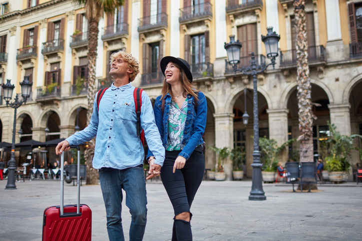 A tourist couple with a suitcase at a new destination.