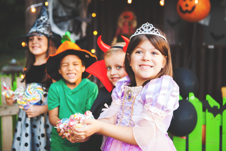 Children in Halloween costumes holding candy.