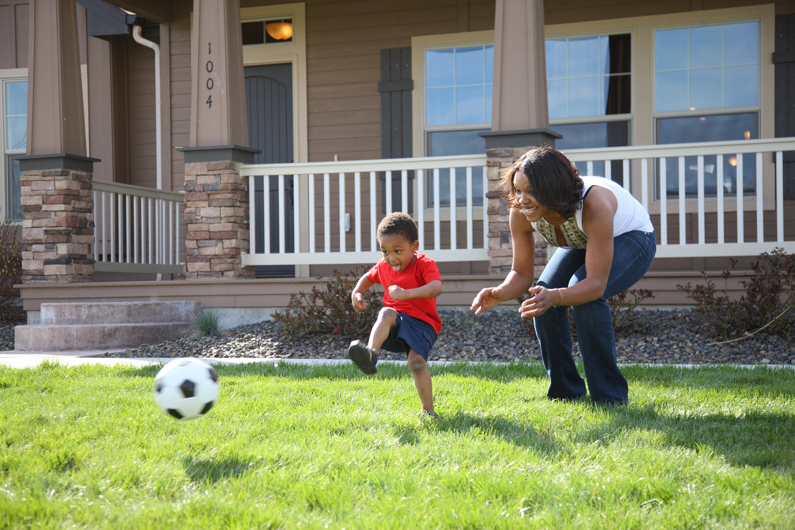 A mother and a son playing soccer in their front yard.