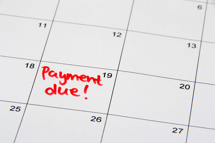 "A calendar with the words ""payment due!"" written on a day."