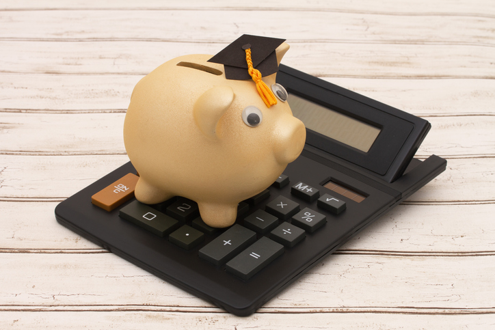 A piggy bank with a graduation cap on sitting on top of a calculator.