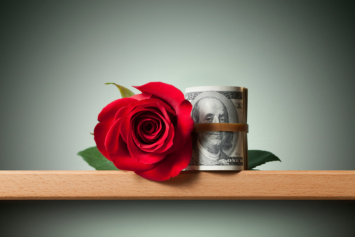 A red rose next to a rolled up $100 bill.