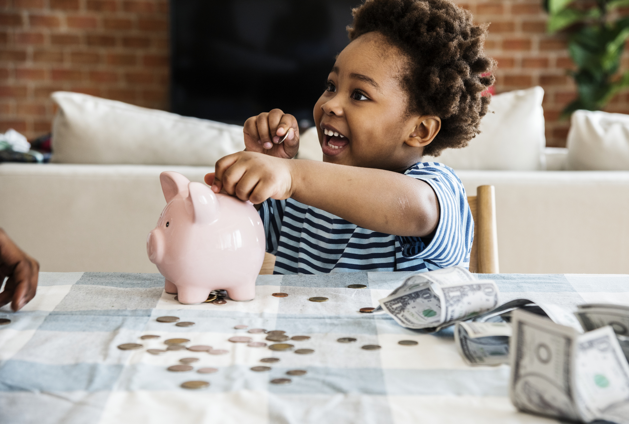 A young child putting money into a piggy bank.