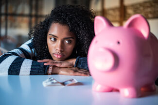 A woman looking longingly at a piggy bank.
