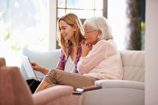 An elderly woman and her daughter sitting on a couch looking at a laptop.
