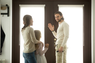 A man waving goodbye to his wife and child.