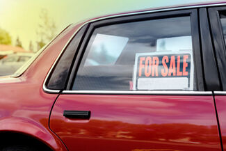"A vehicle window with a ""For Sale"" sign in the window."