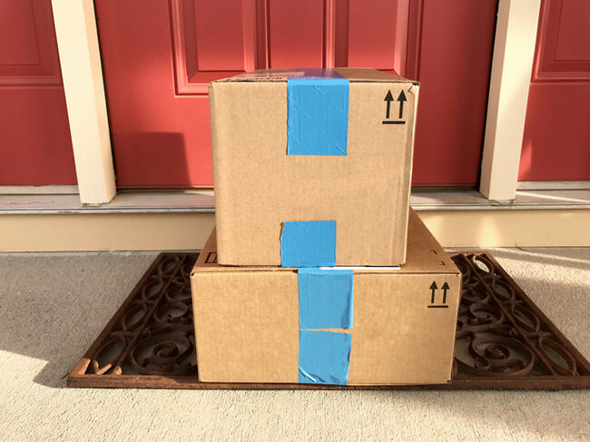 A set of Amazon boxes on a front porch.