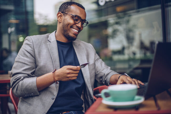 A smiling man at a cafe using his credit card online.
