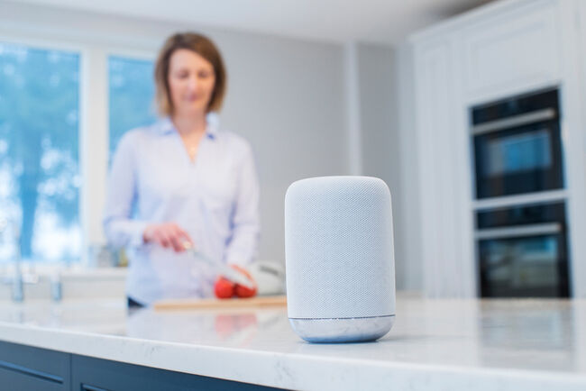 A woman in a kitchen with an Amazon Alexa on the counter.