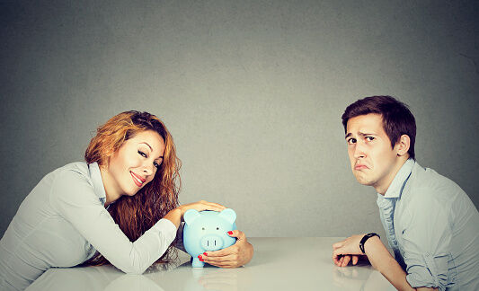 A woman smugly holding a piggy bank across the table from a sad looking man.
