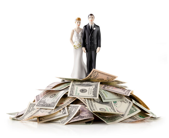A wedding cake topper of a bride and groom on top of a pile of money.