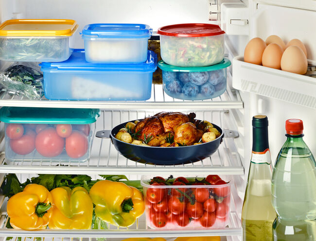 A fridge full of food in Tupperware containers.