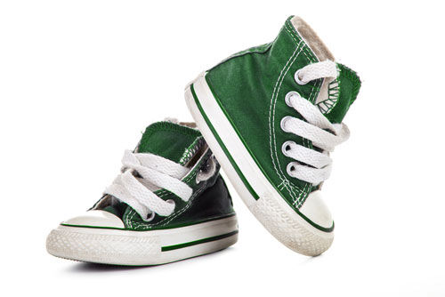 A small pair of green baby Converse shoes.
