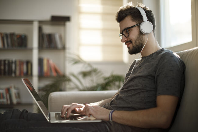 young man on computer wearing headphones