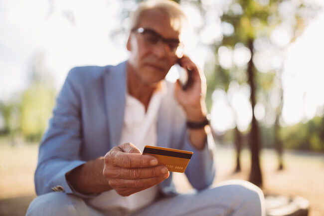 man holding credit card while talking on the phone