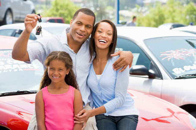 A happy family holding a new set of car keys.