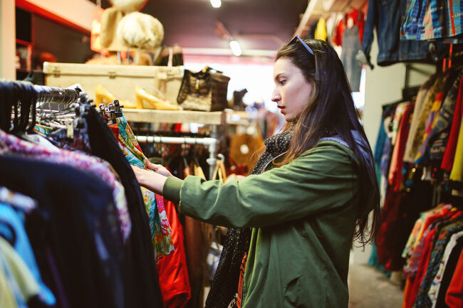 A young woman shopping in a thrift store.