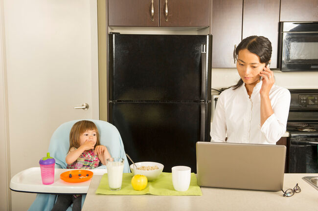 A mom on a laptop and her young daughter in a high chair in a kitchen.