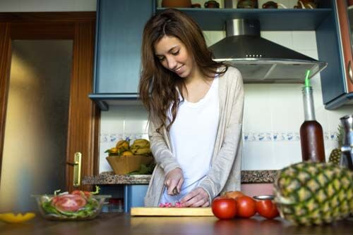 A woman slicing tomatoes on a cutting board.