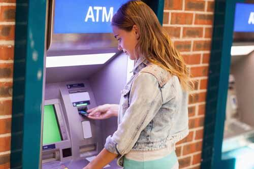 A young woman using an ATM machine.
