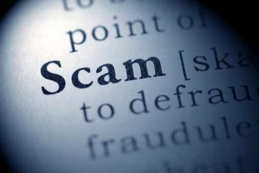 "A close up of the dictionary definition for the word ""scam."""