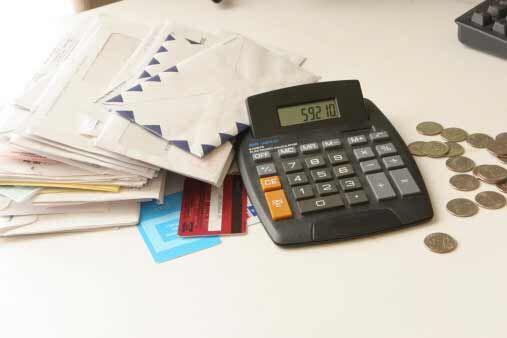 A calculator next to a stack of envelopes and some change.