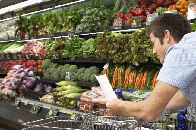A man with a shopping list in the produce aisle of a grocery store.