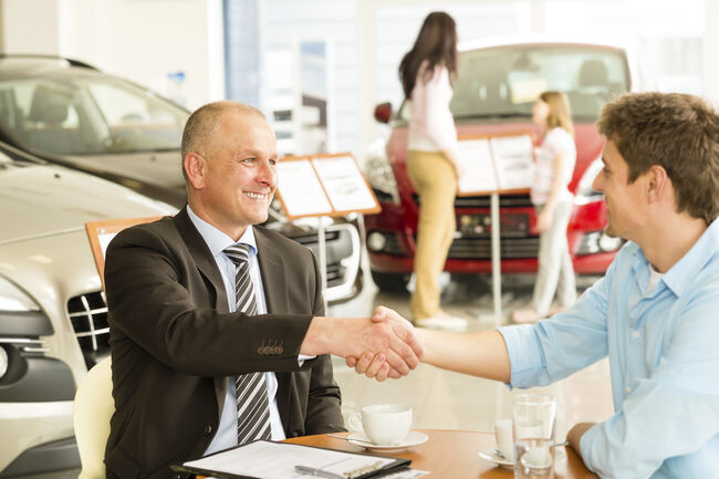 Two men shaking hands inside a car dealership.